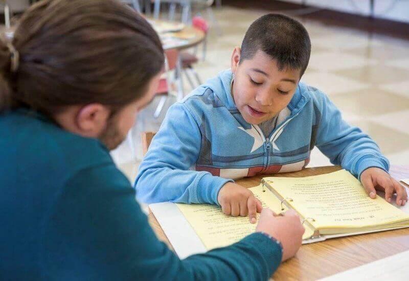 DANA member helping a little boy to read