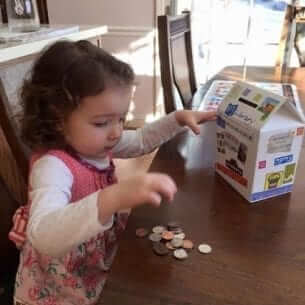 A little girl counting a few coins on the table