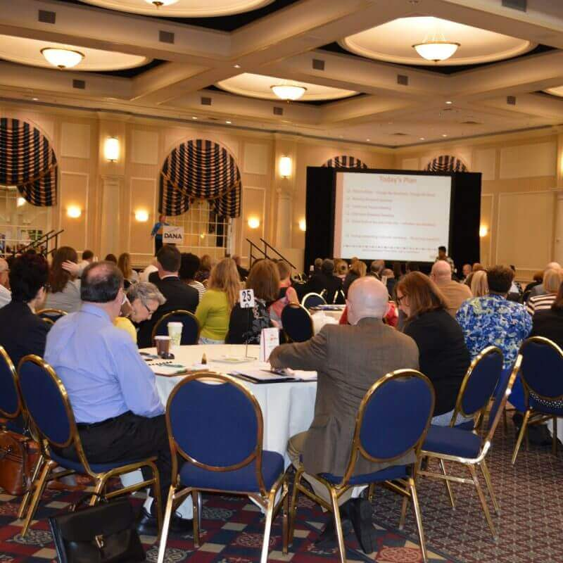 Annual conference attendees listening to the speaker on the podium