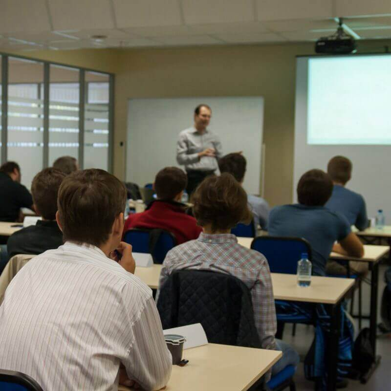 Presenter near the screen and people sitting rear and watching the conference
