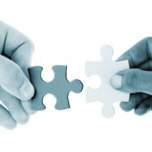 Two hands holding pieces of puzzle image
