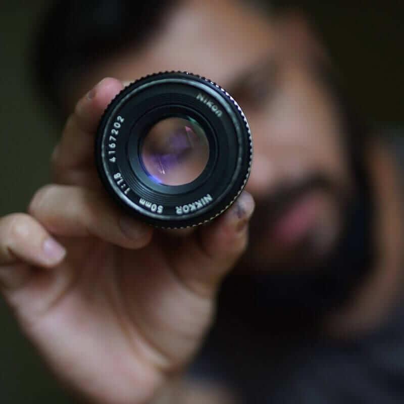 Man holding focused lens